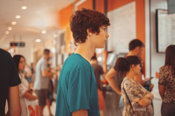 teen standing in a queue